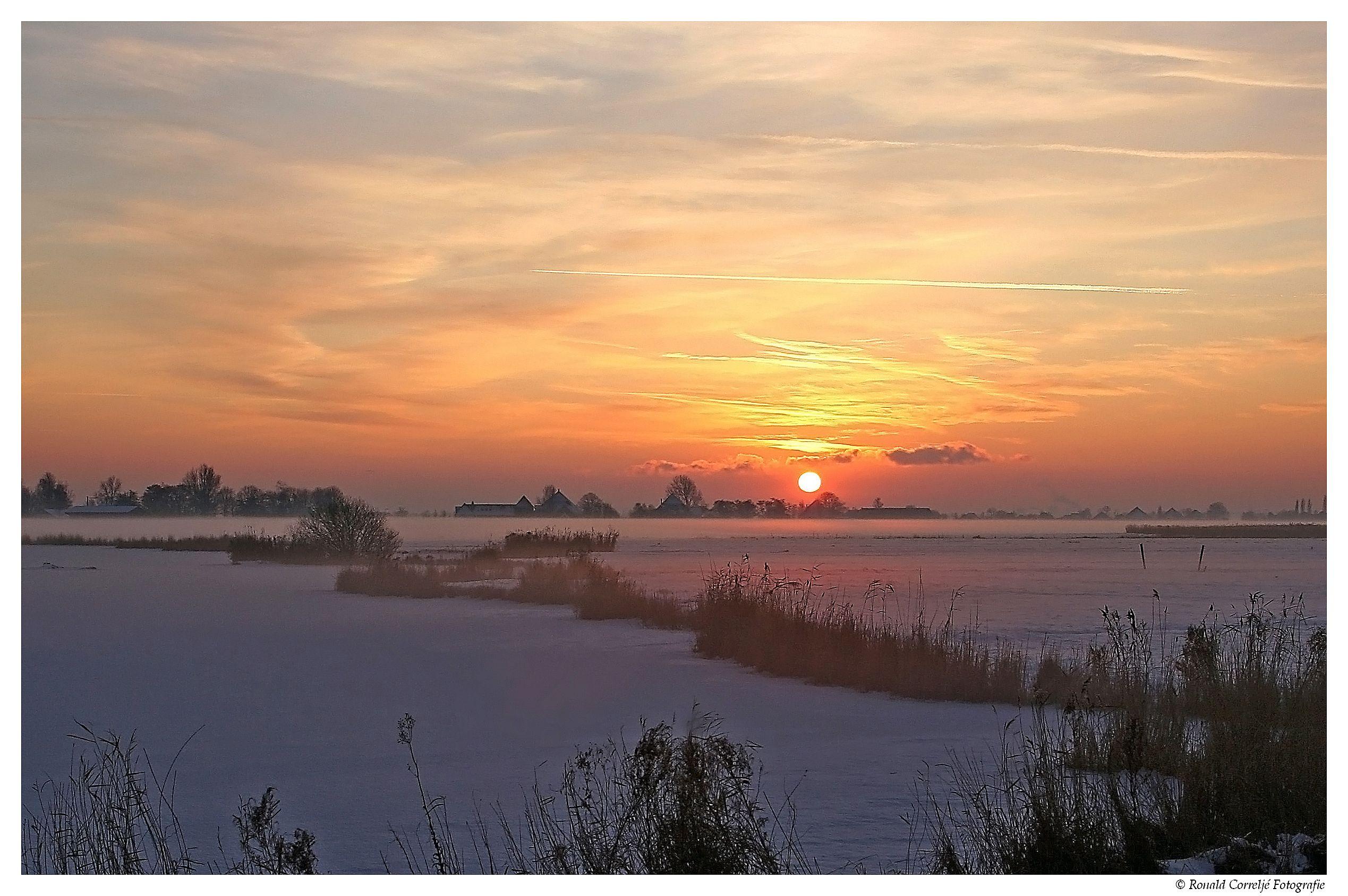 Zonsondergang bij wintersweidelandschap